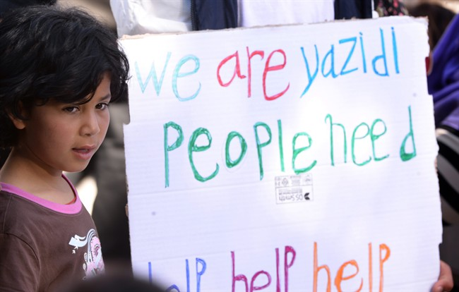 """A child stands next to a placard reading """"We are Yazidi people, Need Help Help Help"""", prior to the arrival of Pope Francis at the Moria refugee camp, on the Greek island of Lesbos, Saturday, April 16, 2016."""