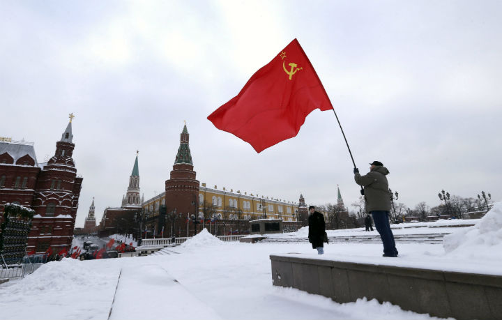 A Russian communist holds a red flag during commemorations for the 92st death anniversary of Soviet founder Vladimir Lenin near his mausoleum on the Red square in Moscow, Russia, 21 January 2016.