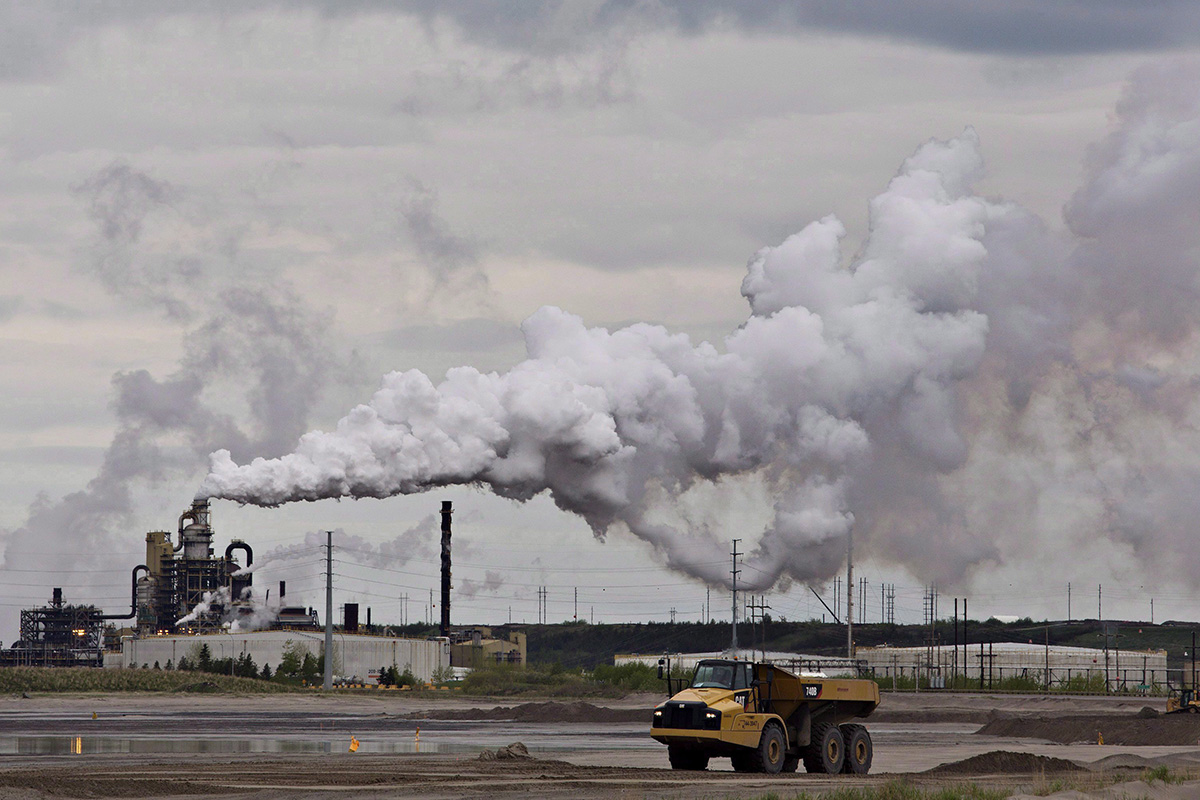 A dump truck works near the Syncrude oil sands extraction facility near the city of Fort McMurray, Alta., on June 1, 2014.