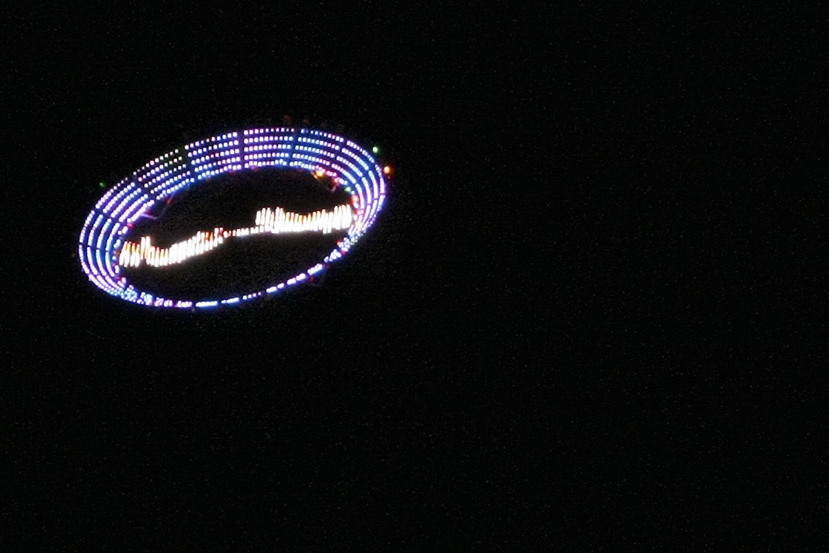 """US plastic artist Peter Coffin's """"Flying Saucer"""" --a 7-meter, LED-studded, SMS-controlled flying saucer and lifted by a helicopter-- overflies Ipanema beach, on May 23, 2009, in Rio de Janeiro, Brazil."""