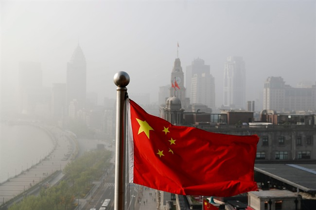 A Chinese national flag flutters against the office buildings at the Shanghai Bund shrouded by pollution and fog in Shanghai, China, Thursday, April 14, 2016.