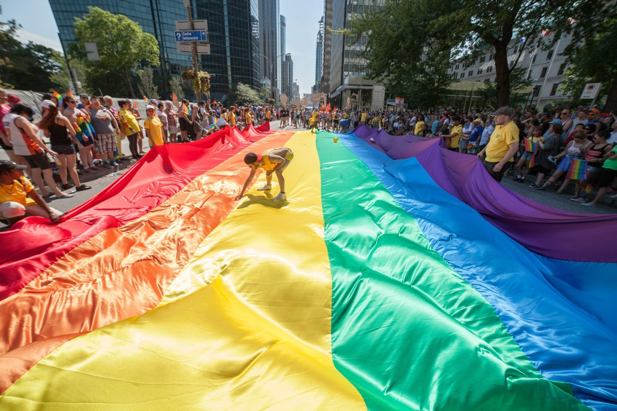 Revelers spread out a giant LGBT flag in the streets of Montreal during the Montreal Pride parade on August 16, 2015.