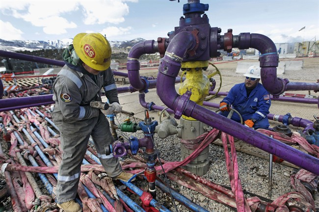 File photo of a worker tending a well head during a hydraulic fracturing operation.