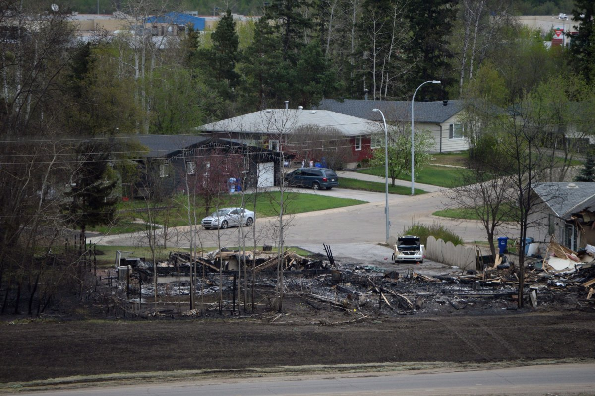 A burned out house and others still intact are shown in the Abasand neighbourhood during a media tour of the fire-damaged city of Fort McMurray, Alta. on Monday, May 9, 2016.