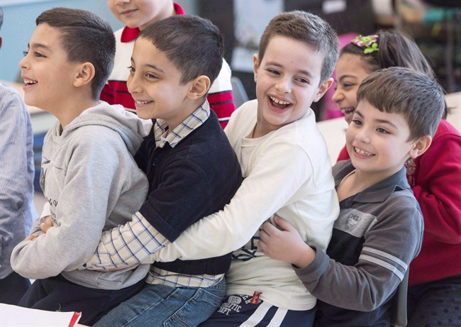 In this 2016 file photo, Syrian refugees Jamil Haddad (left to right), Tony Batekh, George Louka and Edmon Artin have some fun while they attend French classes at a school. Immigration has been a hot-button issue in the Quebec provincial election. Sunday, Sept. 23, 2018.