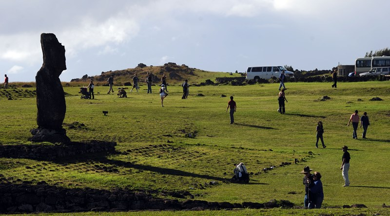 Tourists take pictures of Moais -- stone statue of the Rapa Nui culture -- on Easter Island, 3700 km off the Chilean coast in the Pacific Ocean, on July 9, 2010.