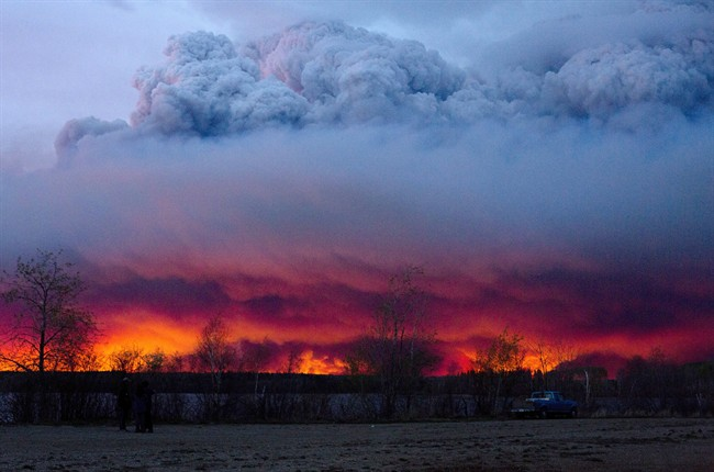 Clouds of ash rise into the atmosphere as fires rage across Fort McMurray.