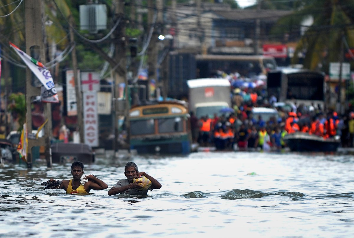 Sri Lankan residents wade through floodwaters in the Kolonnawa suburb of Colombo on May 20, 2016.   Desperate Sri Lankans clambered onto rubber dinghies and makeshift rafts May 20 to flee their homes in the flooded capital Colombo as fresh downpours elsewhere stalled rescue efforts at disaster zones. The heaviest rains in a quarter of a century have pounded the island since last weekend, sparking huge landslides that have buried victims in up to 15 metres of mud.