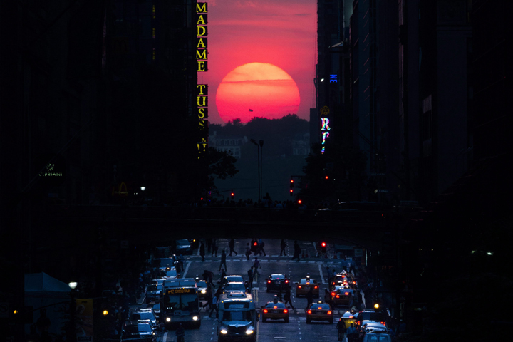 """The sun sets along 42nd Street in Manhattan during an annual phenomenon known as """"Manhattanhenge,"""" when the sun aligns perfectly with the city's transit grid, Wednesday, May 29, 2013, in New York."""