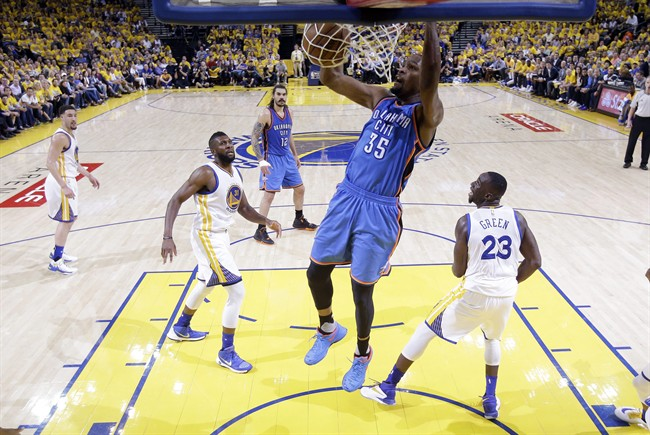 Oklahoma City Thunder's Kevin Durant (35) dunks past Golden State Warriors' Draymond Green (23) and Festus Ezeli (31) during the first half in Game 2 of the NBA basketball Western Conference finals Wednesday, May 18, 2016, in Oakland, Calif.