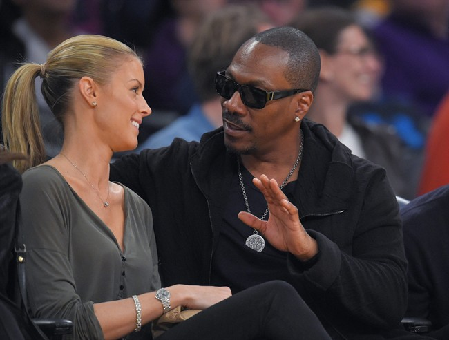 FILE - In this April 12, 2015, file photo, actor Eddie Murphy talks with his girlfriend Paige Butcher during an NBA basketball game between the Los Angeles Lakers and the Dallas Mavericks.