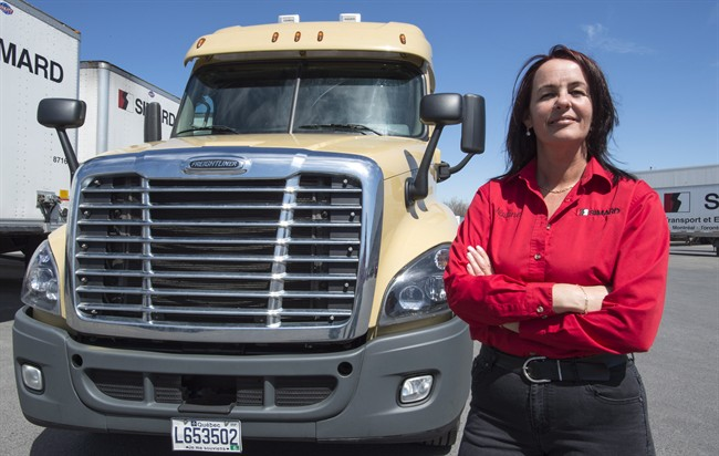 Truck driver Nadine Gauthier stands next to a truck Friday, May 6, 2016 in Montreal. Gauthier, a former truck driver, is working on behalf of Quebec's trucking association to encourage more women and girls to consider careers as truck drivers.