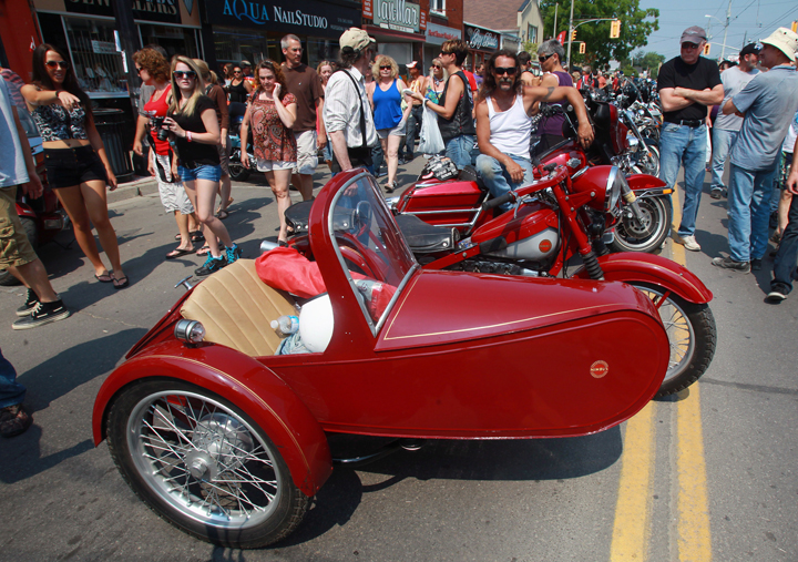 A biker poses with his motorcycle and sidecar in Port Dover, Ont., Friday, July 13, 2012.