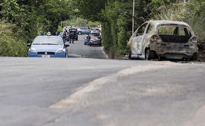 The burned car belonging to slain 22-year-old student Sara Di Pietrantonio is seen along a street in the outskirts of Rome, Monday, May 30, 2016.