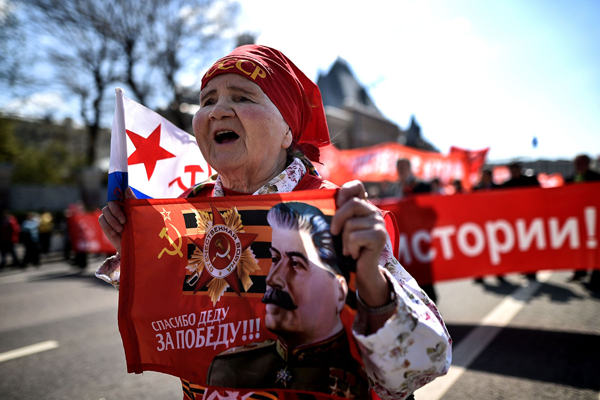 A Russian Communist party activist carries a banner with an image of late Soviet leader Joseph Stalin during a May Day rally in central Moscow on May 1, 2016.