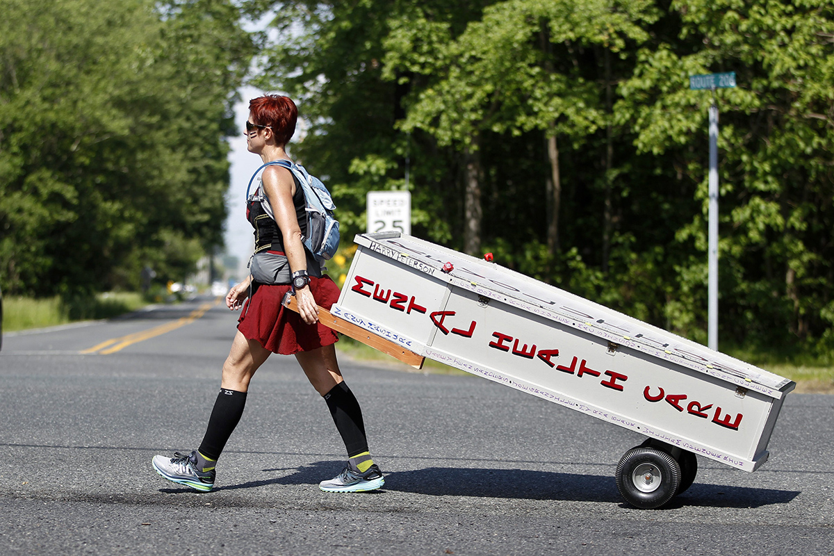 Greta Schwartz, of Seaville, N.J., is dressed like a Spartan warrior pulling a casket as she walks along route 206, from southern New Jersey to Trenton Tuesday, May 31, 2016, in Tabernacle, N.J.