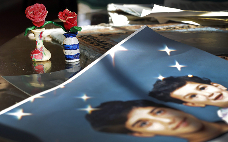 Prison artwork created by Adnan Syed sits near family photos in the home of his mother, Shamim Syed, in Baltimore.