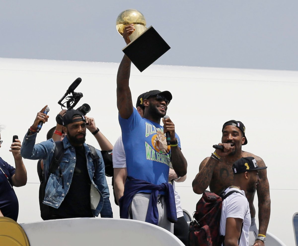 Cleveland Cavaliers' LeBron James holds up the Larry O'Brien Trophy after arriving in Cleveland, Monday, June 20, 2016. James came home with the trophy he promised, and the championship Cleveland has coveted for 52 years. The NBA superstar, born and raised in nearby Akron, stepped off a plane Monday and hoisted the shiny Larry O'Brien Trophy as more than 10,000 fans celebrated the city's first title since 1964.
