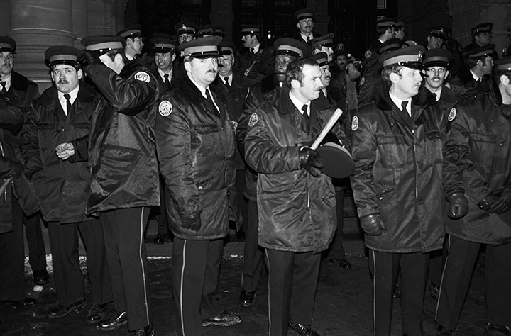 Police officers stand on the steps of the Ontario Legislature in Toronto in the early hours of Feb. 7, 1981 after gay rights demonstrators marched there in protest of the arrests of hundreds of men on Feb. 5, 1981 of in four city bathhouses.
