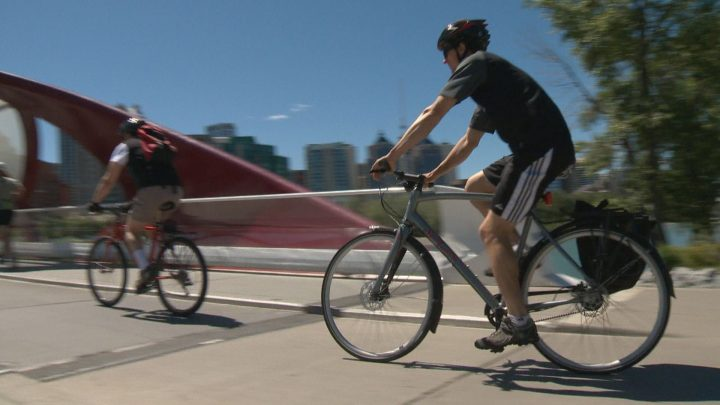 A Calgary couple cycle downtown during the noon hour on Wednesday.