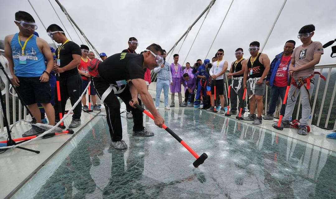 A man swings a hammer against the glass bridge.