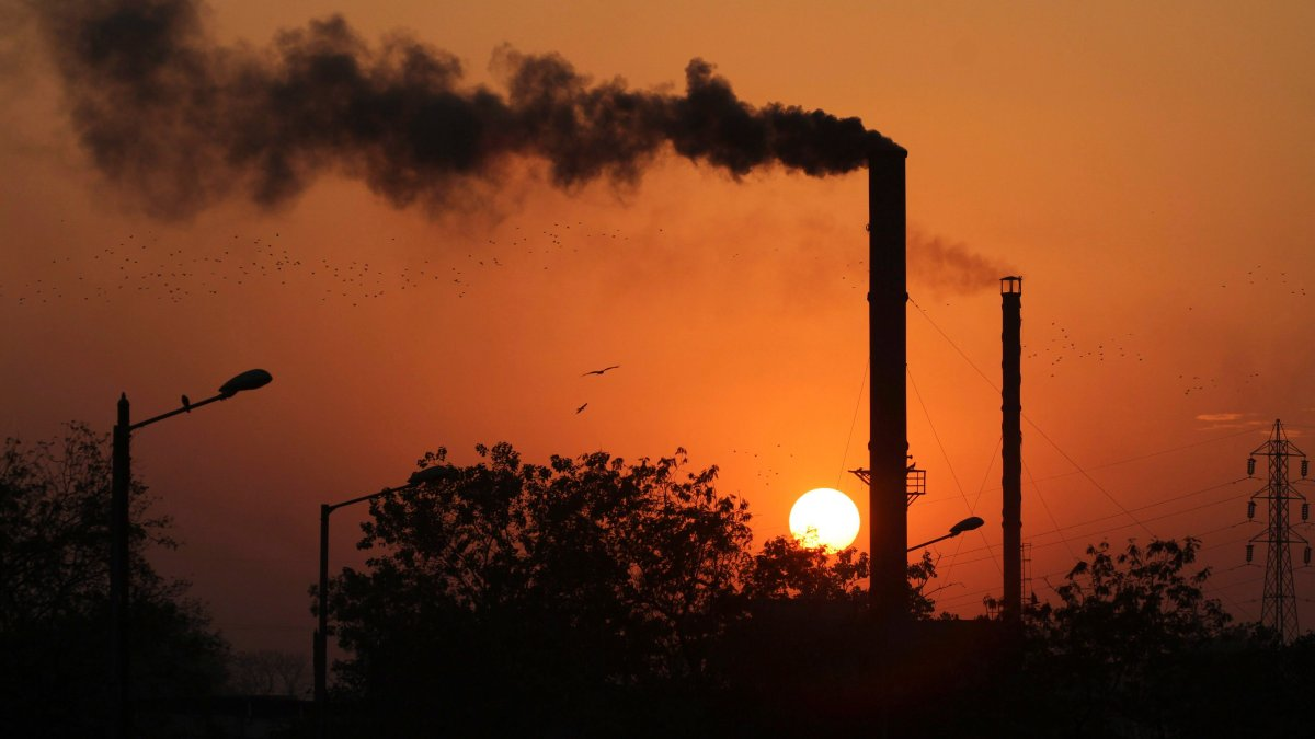 This is a Monday, Dec. 8, 2014 file photo of birds as they fly past at sun set as smoke emits from a chimney at a factory in Ahmadabad, India.