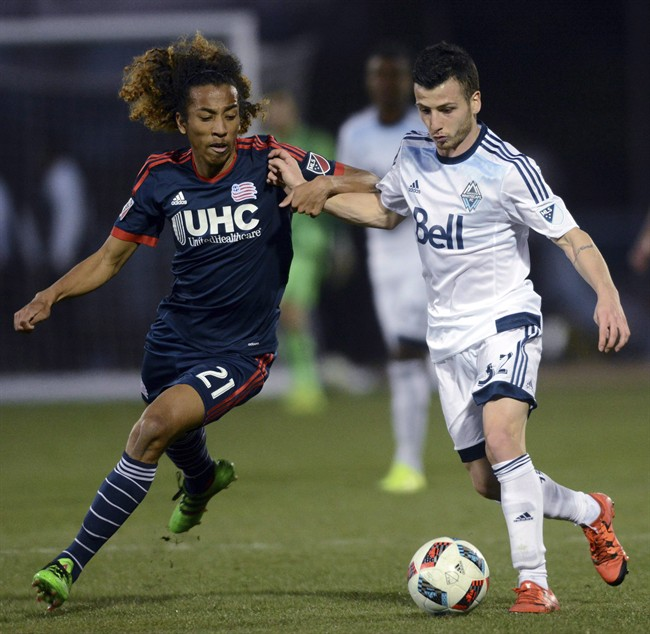 New England Revolution midfielder Zachary Herivaux and Vancouver Whitecaps midfielder Marco Bustos vie for possession during an MLS preseason soccer game on Feb. 6, 2016.