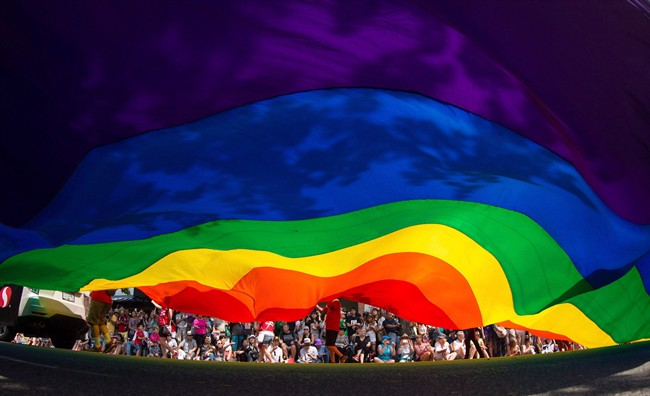 A large rainbow flag is carried down Robson Street during the Vancouver Pride Parade in Vancouver, B.C., on Sunday, August 2, 2015.