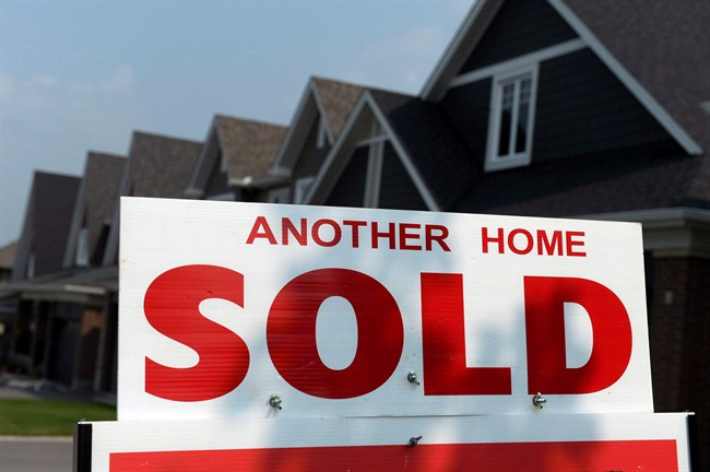 A for sale sign displays a sold home in a development, in Ottawa, on July 6, 2015.