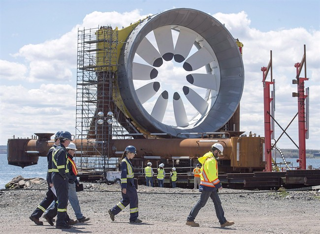 Workers head past a turbine for the Cape Sharp Tidal project at the Pictou Shipyard in Pictou, N.S., on Thursday, May 19, 2016. The need for more consultation and permits has temporarily pulled the plug on plans to install the first of two towering turbines designed by Cape Sharp Tidal to harness the power of the Bay of Fundy.THE CANADIAN PRESS/Andrew Vaughan.