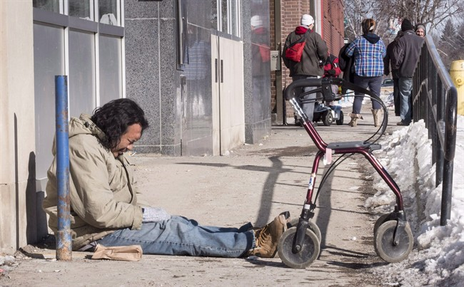 Lefty, who is homeless, sits on a sidewalk in downtown Thunder Bay, Ontario.