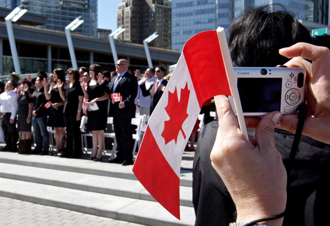 A woman takes a photograph while holding a Canadian flag during a citizenship ceremony in Vancouver, B.C., on July 1, 2009.