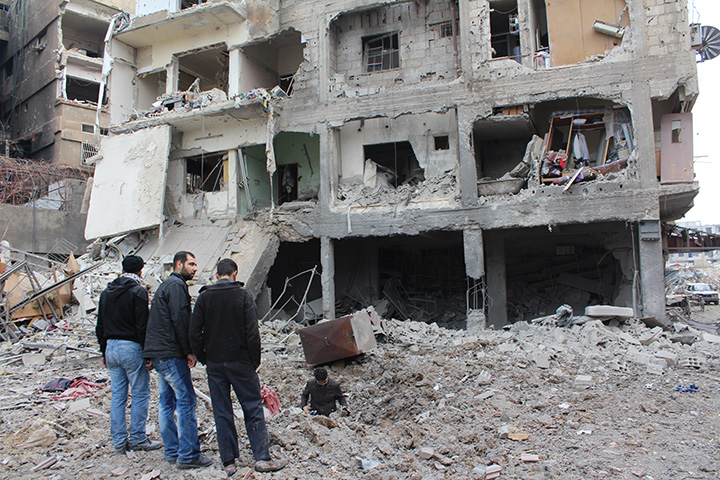 In this January 12, 2014 file photo, residents are seen outside of a destroyed building in the city of Daraya, southwest of the capital Damascus.