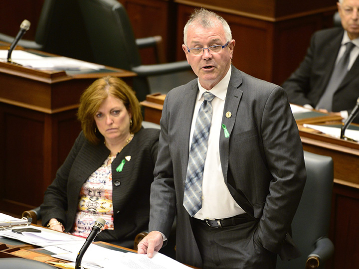 Ontario Labour Minister Kevin Flynn tables back to work legislation for striking secondary school teachers at the legislature in Toronto, Monday, May 25, 2015 as Liberal MPP Eleanor McMahon looks on.