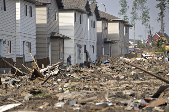 A resident of Fort McMurray, Alta, looks at the damage to homes on Thursday, June 2, 2016. Fires like the one that devastated the city are likely to become more frequent as a result of climate change, scientists have predicted.