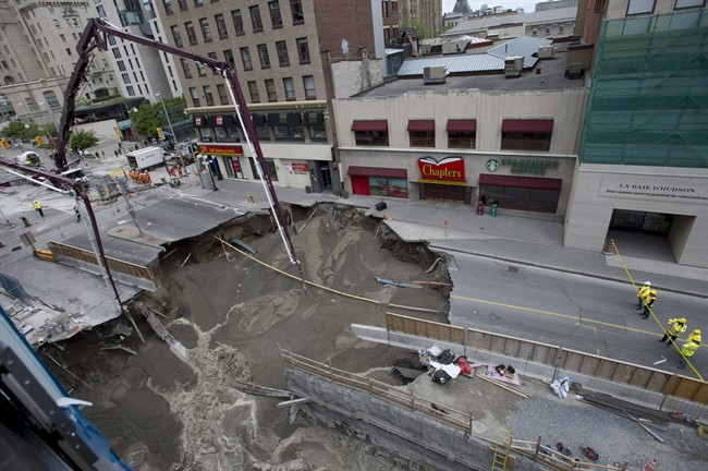 Workers look on as boom concrete pumps fill a large sinkhole that formed Wednesday morning on Rideau Street, Thursday, June 9, 2016 in Ottawa.