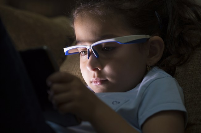 Liliya Sahiholnasab, 6, uses a special pair of glasses to help her correct her posture when using a tablet at her home in Richmond, B.C., Wednesday, June, 22, 2016. Dr. Vahid Sahiholnasab has designed a pair of high-tech glasses to prevent children from developing bad posture while playing with devices like smartphones and video games.
