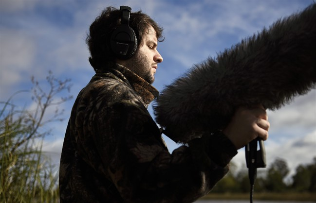 In this June 1, 2016 photo, Juan Pablo Culasso holds a microphone in a natural reserve on the outskirts of Montevideo, Uruguay. Although Culasso can distinguish light, allowing him to differentiate night from day, he cannot register shapes, forms, and even less so the colors of birds. His ears have always been his way to connect more profoundly with the world. His ability to recognize and record nature's sounds has landed him jobs working for documentary soundtracks. (AP Photo/Matilde Campodonico).