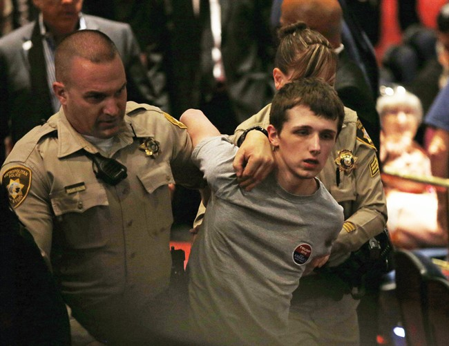 In this June 18, 2016, photo, police remove Michael Steven Sandford as Republican presidential candidate Donald Trump speaks at the Treasure Island hotel and casino in Las Vegas.