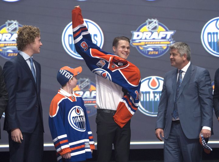 Jesse Puljujarvii, fourth overall pick, pulls on his sweater as he stands on stage with members of the Edmonton Oilers management team at the NHL draft in Buffalo, N.Y. on Friday June 24, 2016.
