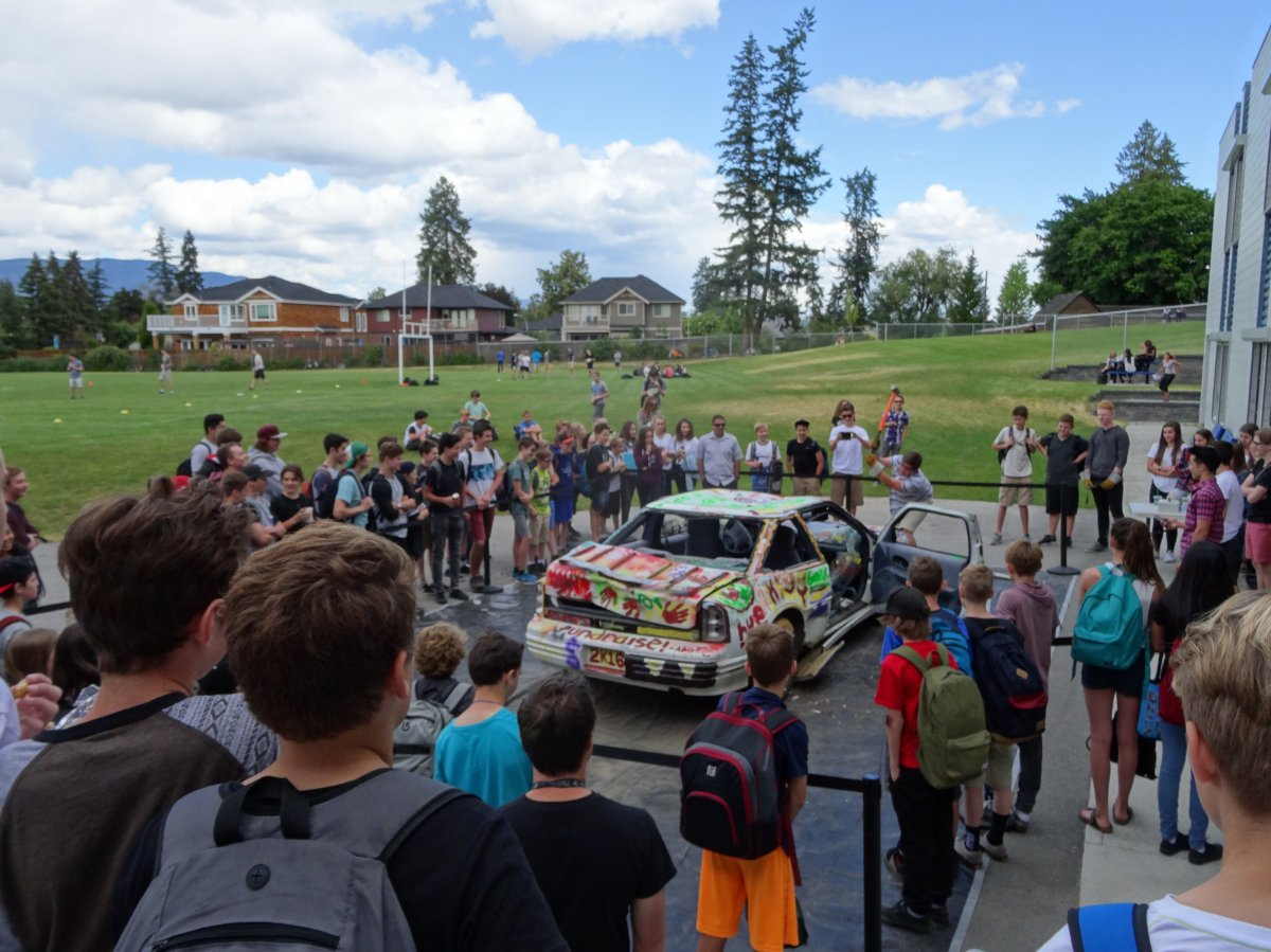 A car being smashed at Okanagan Mission Secondary school to raise money for Fort McMurray.