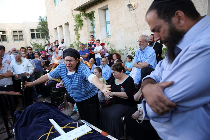 Rina Ariel weeps over the body of her slain 13 year old daughter Hallel during her funeral inside a Jewish settlement of Kiryat Arba, West Bank, Thursday, June 30, 2016.