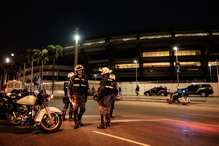 Brazilian federal police officers close the road during the security drill for the transfer of athletes at Maracana Stadium which will host soccer matches for Rio 2016 Olympic Games on June 19, 2016.