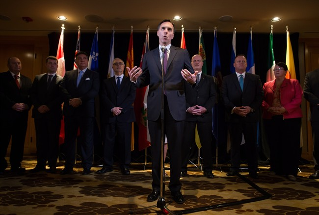 Federal Finance Minister Bill Morneau, centre, is flanked by his provincial and territorial counterparts as he speaks during a news conference after reaching a deal to expand the Canada Pension Plan, in Vancouver, B.C., on Monday June 20, 2016.