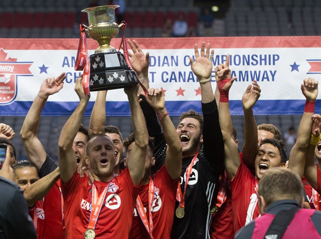 Toronto FC's Benoit Cheyrou, left, and his teammates celebrate with the Voyageurs Cup after defeating the Vancouver Whitecaps on aggregate in the Canadian Championship soccer final in Vancouver, B.C., on Wednesday June 29, 2016.
