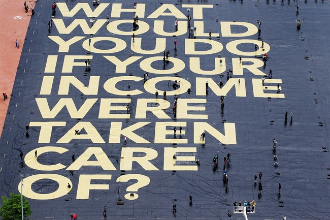 """In this May 14, 2016 file picture a huge poster reading """"What would you do if your income were taken care of?"""" is pictured on the Plaine de Plainpalais square in Geneva."""