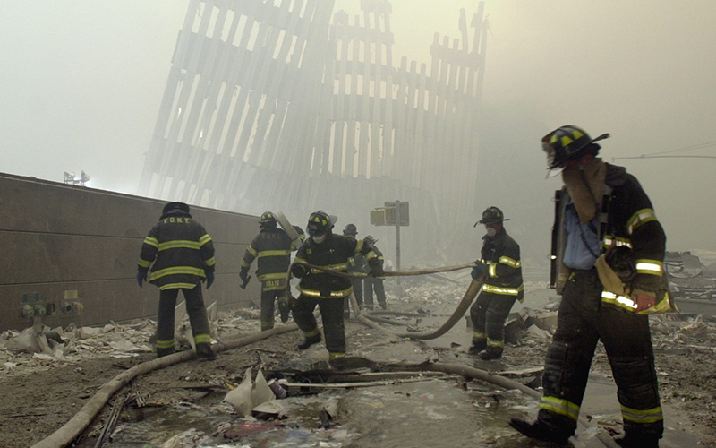 Firefighters work beneath the destroyed mullions, the vertical struts which once faced the soaring outer walls of the World Trade Center towers.