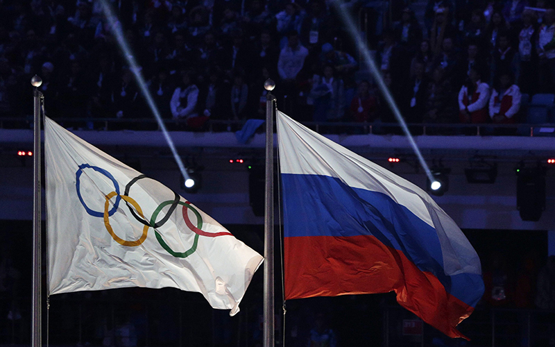 The Russian national flag flies next to the Olympic flag during the closing ceremony of the 2014 Winter Olympics in Sochi, Russia.