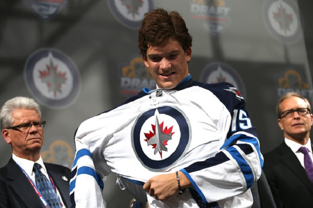 Jack Roslovic puts on a jersey after being selected 25th overall by the Winnipeg Jets during the first round of the 2015 NHL Draft at BB&T Center in Sunrise, Florida.