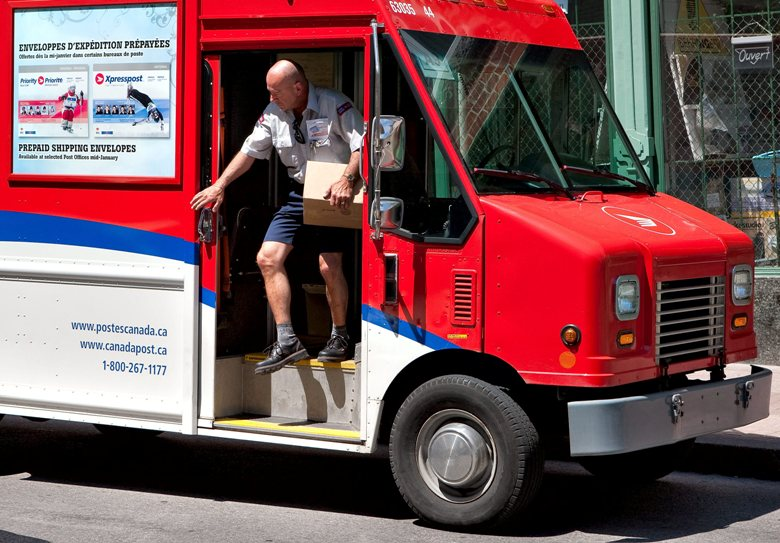 A Canada Post worker gets out of his delivery truck with a box in his hand.